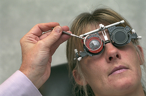 Optician fitting lenses onto a patient